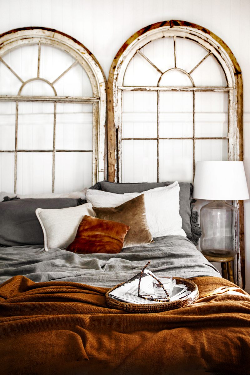 Rustic Bohemian Interior Design in a Vintage Cottage bedroom with fall colors and warm russet tones. Salvaged arched windows serve as the headboard. #rustic #boho #bedroom #vintage #interiordesign #cognac #fallcolors