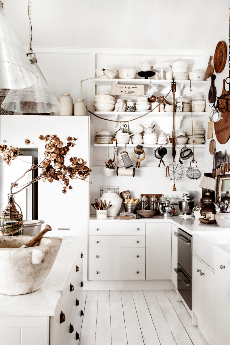 Rustic Bohemian Interior Design in a Vintage Cottage. White cottage kitchen with open shelves full of vintage essentials. #whitekitchen #farmhousekitchn #cottagestyle #shelves