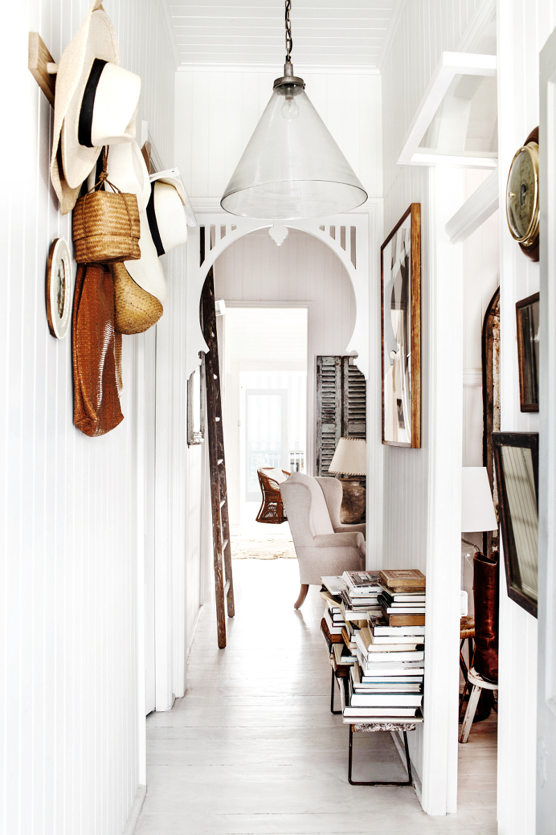 Rustic Bohemian Interior Design in a Vintage Cottage with white by Kara Rosenlund. White painted paneling in a hallway with rustic decor and vintage treasures. #rusticdecor #whitedecor #cottagestyle #hallway