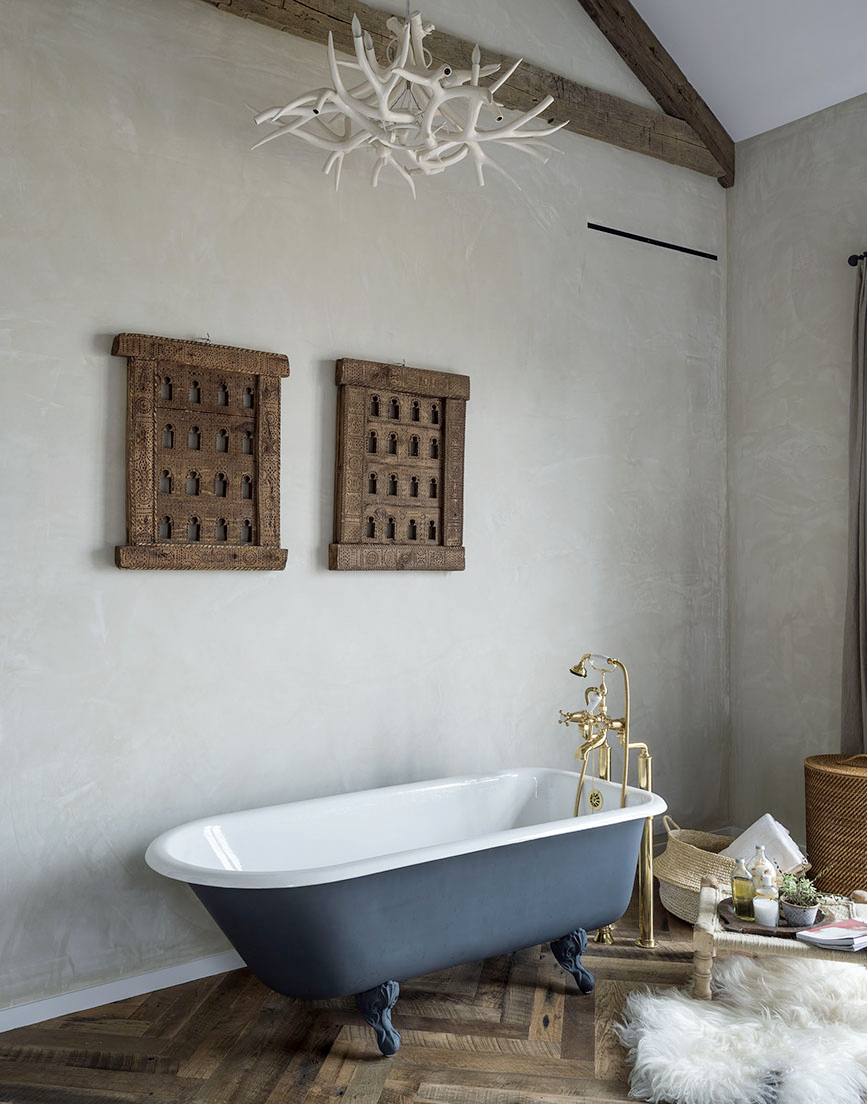 Venetian plaster walls, Moroccan art, clawfoot tub, and antler chandelier in country bathroom with #rusticdecor