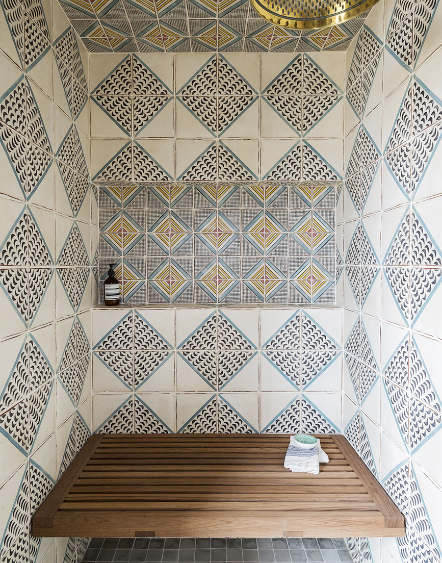 Magnificent Moroccan tiles with diamond pattern in a shower with teak wood seat