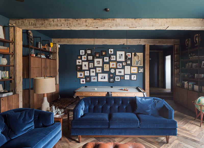 A mix of blues in a rustic modern lounge with pgrey ool table, teal art gallery wall, and royal blue velvet sofas