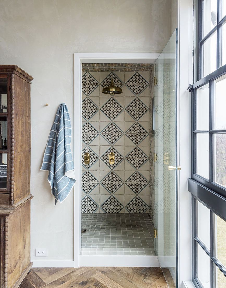 Brass shower fixtures, Moroccan tiles with diamond pattern, and square mosaic shower floor in #modernfarmhouse bathroom