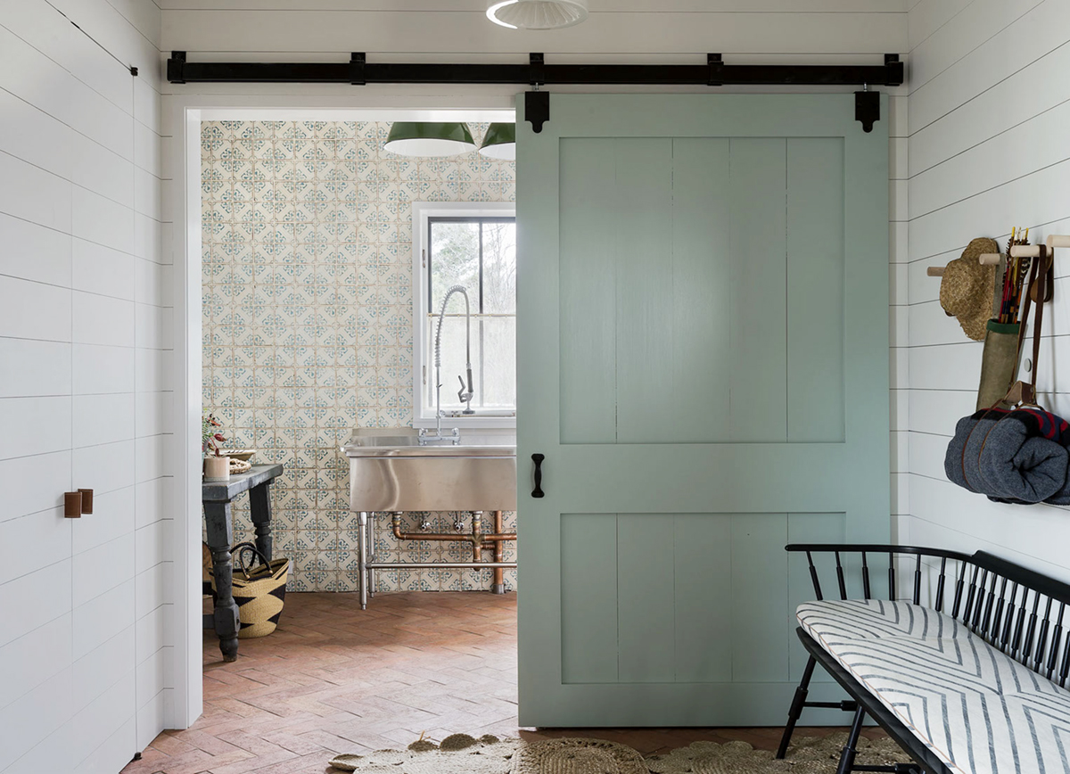 Green sliding barn door and shiplap walls in entry to mudroom with commercial stainless sink
