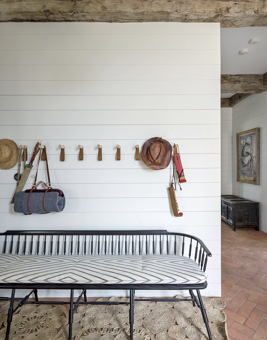 Wood bench against shiplap wall with peg hooks in entry of #modernfarmhouse
