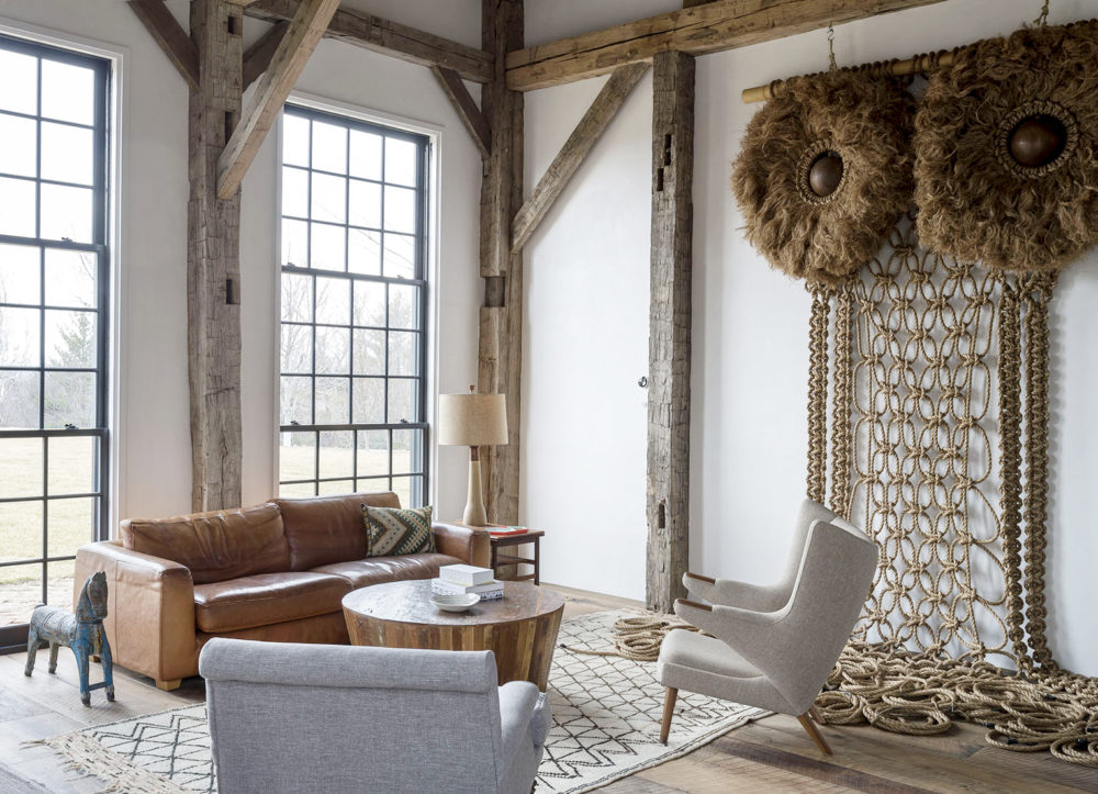 Giant macrame owl in rustically elegant modern farmhouse den with black windows and wood beams