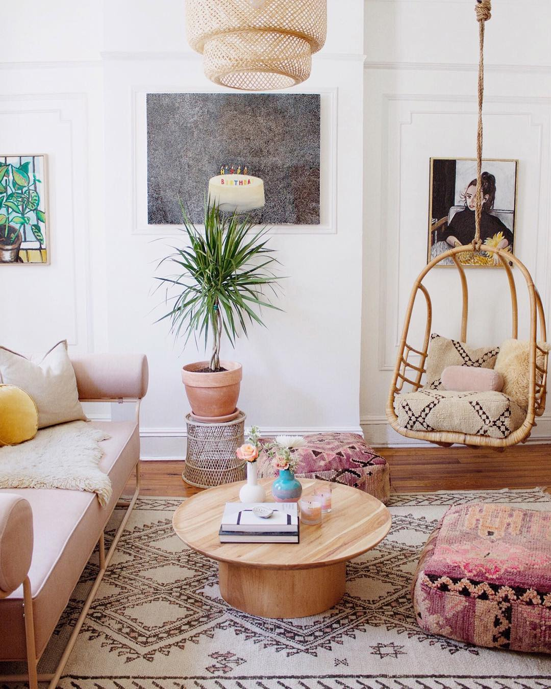 Living room with pink accents, beachy decor, and wicker swing. Boho Chic Pretty in Pink Apartment. #livingroom #boho #apartment #pink #tribal